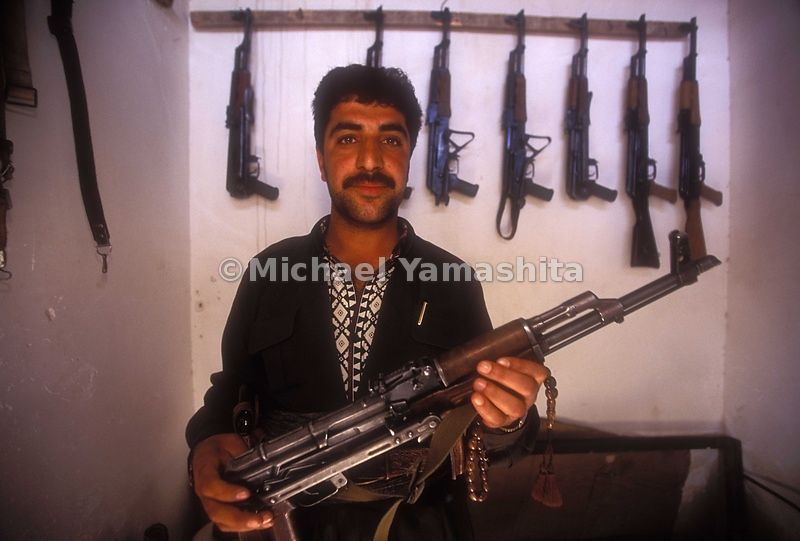 An Iraqi man holds an AK-47 assault rifle in his store.