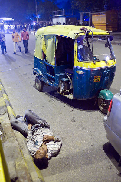 India - Delhi - A man lies drunk at the side of a road
