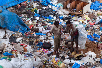 Men collect recycling from a garbage pile in Bandra East, Mumbai, India.