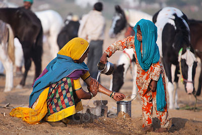 A girl helps her mother wash her hands at a water spigot in the desert, Pushkar, Rajasthan, India.