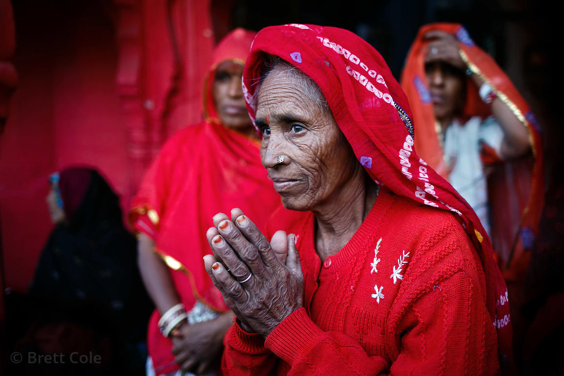 An elderly woman prays during pilgrimage in Pushkar, Rajasthan, India