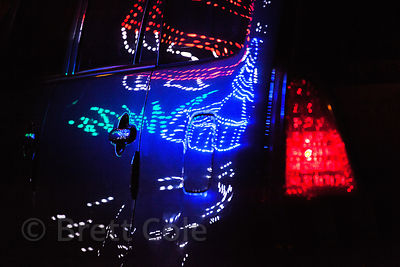 Lights from a Durga Puja display reflect in a car's exterior in Lake Gardens, Kolkata, India.