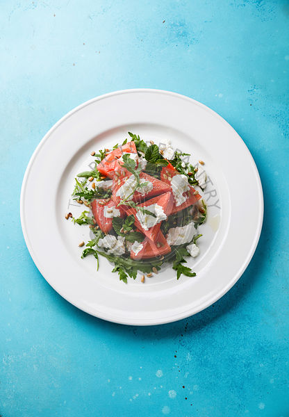 Watermelon salad with arugula, ricotta cheese and mint on blue background