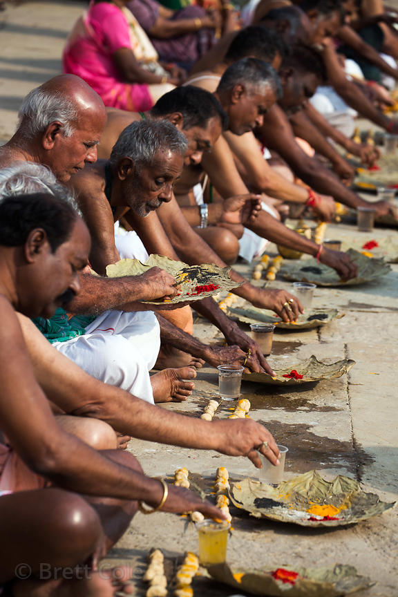 Hindu men pilgrims perform rituals dedicated to honoring deceased relatives, while their wives stand behind watching, Unknown...