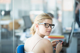 Blonde business trainee with her pink phone looking at camera. She is wearing a white top and watches and trendy glasses. She...