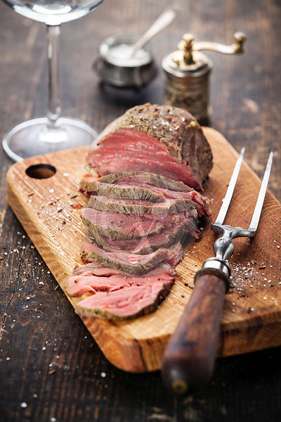 Roast beef on cutting board with meat fork, saltcellar and pepper mill