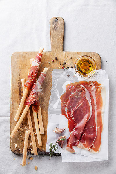 Bread sticks with ham on wooden cutting Board