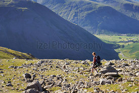 A female hiker backpacking In the English Lake District with views of Kirk Fell and Mosedale.