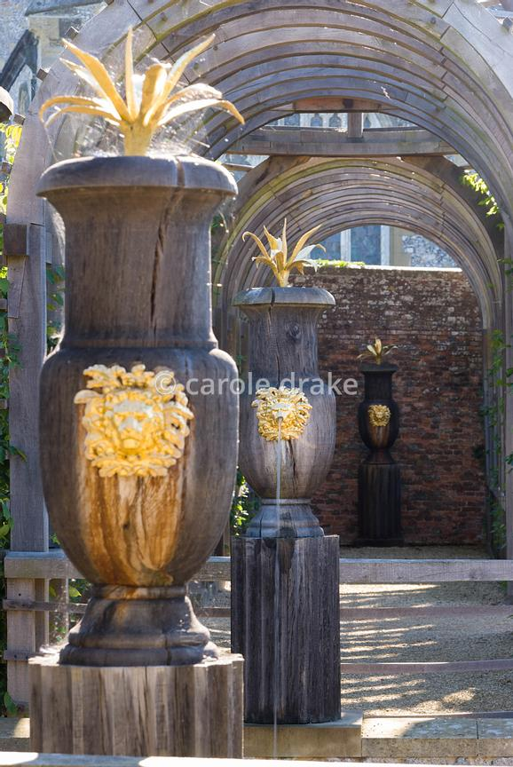 Carved oak urns with gilded lions' heads and agaves with domed pergola beyond in the Collector Earl's Garden designed by Juli...