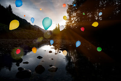 Balloons floating over still rocky lake