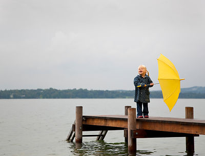 Girl holding yellow umbrella on dock