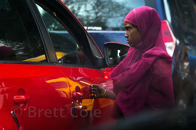 A girl asks motorists for money at an intersection in Lake Gardens, Kolkata, India.