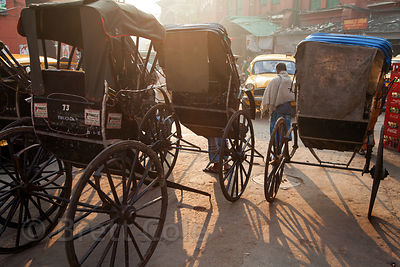 Rickshaws on the streets of Newarket at sunrise, Kolkata, India.