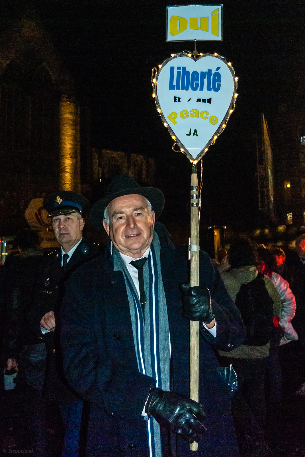 Amsterdam, Netherlands 2015-01-08: Man holding a two-sided sign - YES - side, and the Chief commissioner of Police Amsterdam
