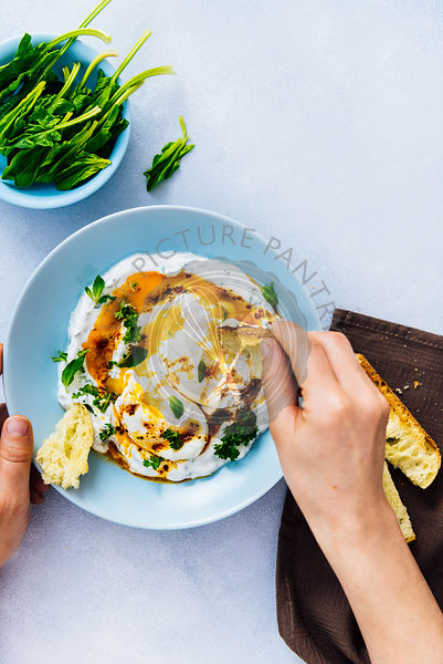Woman eating Turkish eggs with some toasted bread. Baby spinach in a small blue bowl accompanies.
