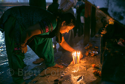 A woman lights candles along the Ganges River while observing Diwali in Haridwar, India