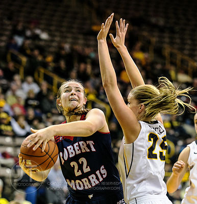 Robert Morris' Megan Smith (22) looks to shoot over Iowa's Kali Peschel (25) during the first half of play at Carver-Hawkeye ...