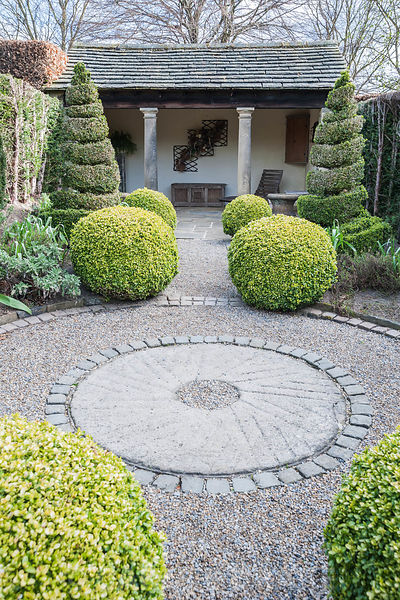The Herb Garden with topiary box and yew shapes, a summerhouse at one end, and a central gravel path edged with stone setts. ...