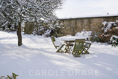 Snowy garden with teak table and chairs left out over winter
