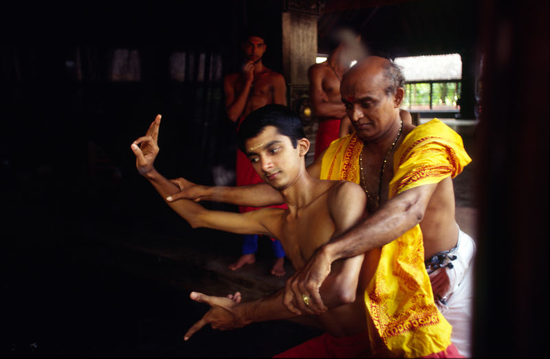 India - Kerala - In a mirror, Professor Balasubramanian, a senior teacher of Kathakali shows a student a difficult step in cl...