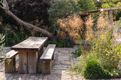 Chunky oak table and benches on a sunny terrace beside the house, with Stipa gigantea, Verbena bonariensis and salvias in adj...