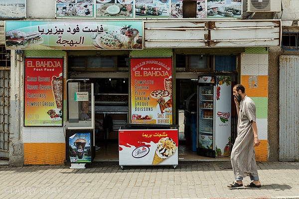 Local man walking past fast food shop in Algiers, Algeria, North Africa