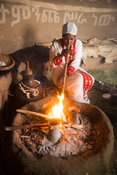 Woman blowing fire for coffee ceremony, Ankober, Ethiopia