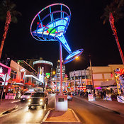 View looking up towards a giant martini glass in blue neon on Fremont Street with passing cars, Las Vegas, Nevada, USA