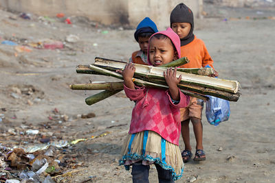 A girl carries pieces of bamboo with nails in them across the uneven, trash-strewn, muddy bank of the Ganges River at the Har...