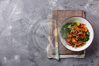 Udon stir fry noodles with Chicken meat and vegetable in bowl on concrete background copy space