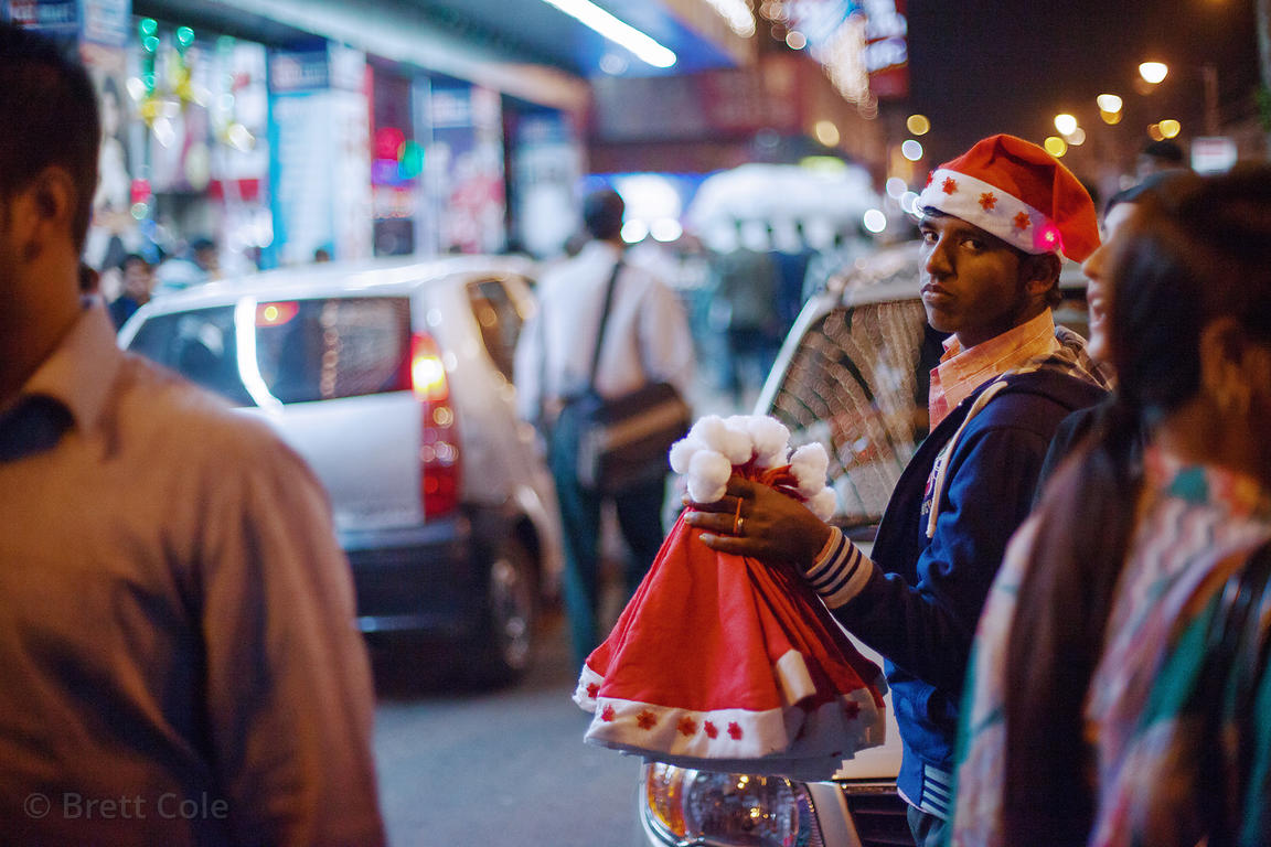A mans sells Santa hats at Christmas time in Newmarket, Kolkata, India.