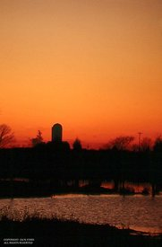 Silo. lake and red sky