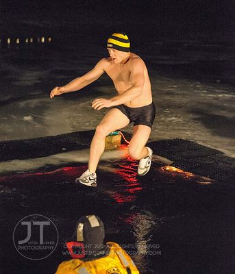Ryan Morningstar jumps into the frigid water during the Hawkeye Wrestling Club's Polar Plunge at the Brown Deer Country Club ...