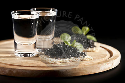 served place setting: vodka and sandwiches with black caviar on black background