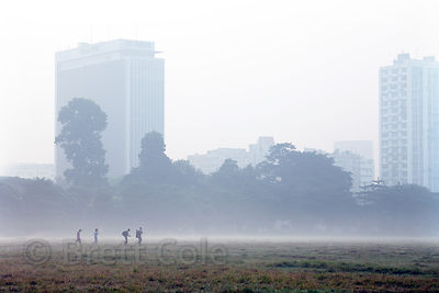 Cricket players walk to their field on a misty morning on the Maidan, a large park in central Kolkata, India.