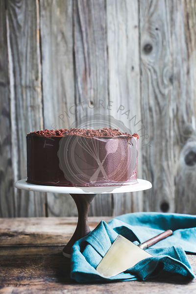 Chocolate cake on a cake stand against a wooden background