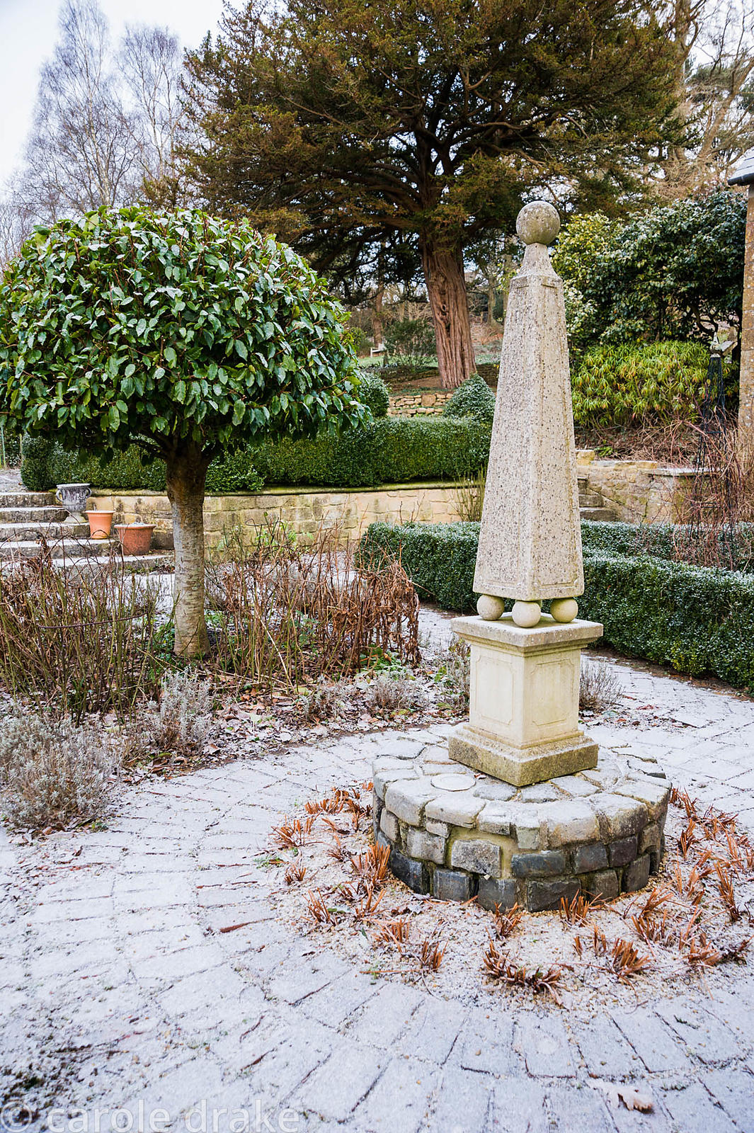 A stone obelisk marks the centre of the courtyard garden surrounded by clipped standard bays and box edged beds.