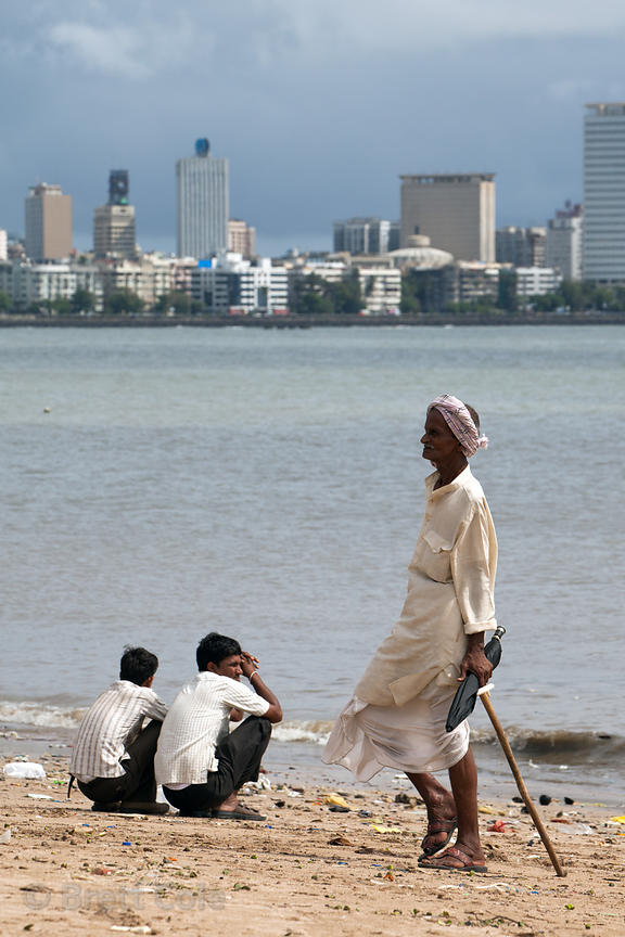 A man walks on Chowpatty Beach, Mumbai, India, with Back Bay (Arabian Sea) in the background.