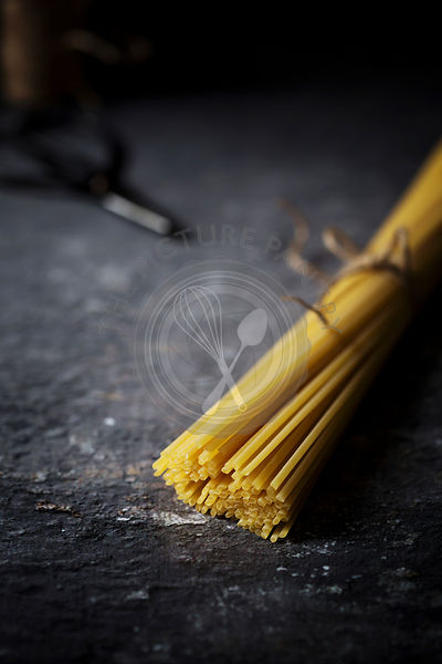 Close-up of raw spaghetti on dark background
