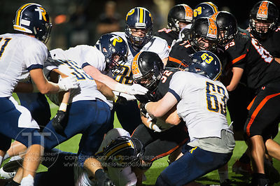 Iowa City Regina's Alexander Moore (63) wraps up Solon's Adam Bock (32) during the first half of play in Solon on Friday, Sep...