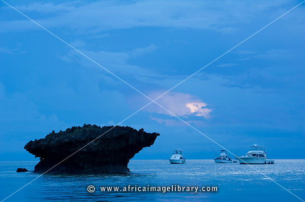 Fishing boats next to a coral outcrop at sunrise, Turtle Bay, Watamu, Kenya