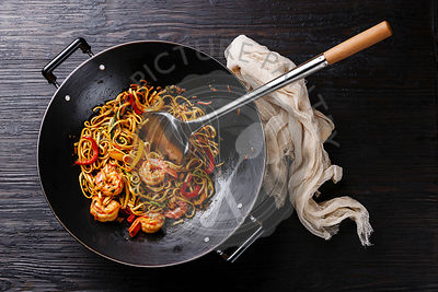 Udon stir fry noodles with prawn shrimp and vegetables in wok pan on black burned wooden background