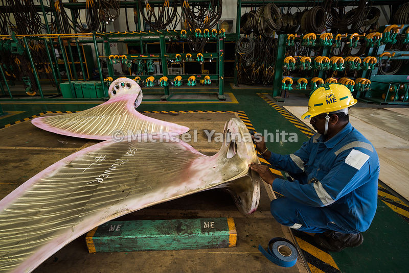 An employee of Semcorp Marine, another major force in the offshore and marine sector, marks a ship propeller for easy identif...