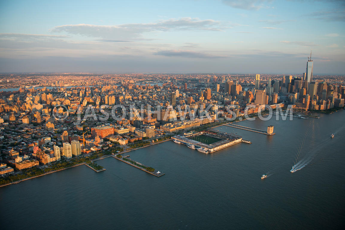 Aerial view looking across Lower Manhattan, showing a soccer field on the Hudson River and One World Trade Center in the dist...