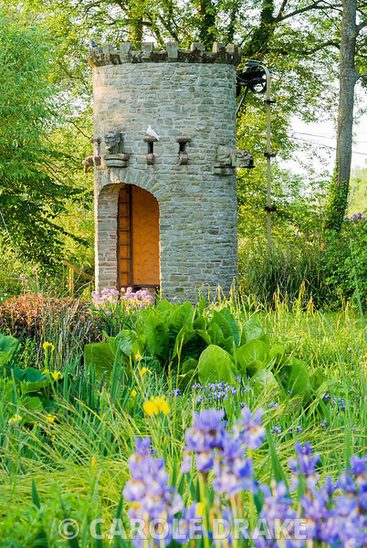 Stone dovecot that operates as a spectacular water feature with Iris sibirica in foreground. A simple belt and trough system ...