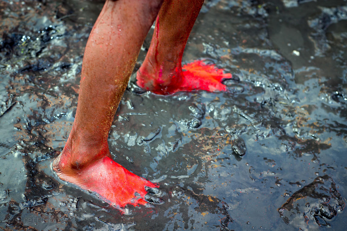 A boy's feet are covered in orange gulal powder during immersion of Ganesh idols in the Yamuna River during the Ganesh Chatur...