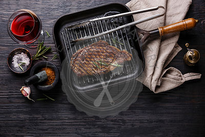 Grilled Steak Striploin on pan and red wine on black burned wooden background copy space