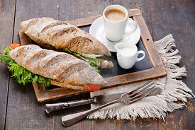Sandwich with smoked salmon and coffee on vintage slate chalk board background