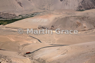 A lorry on the Arica to La Paz (Bolivia) road as it snakes uphill through ultra-arid desert, Upper Lluta Valley, northernmost...
