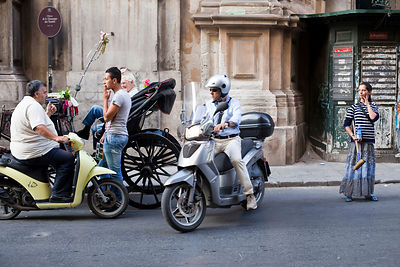 Italy - Palermo - On the streets a Gypsy woman waits to was cars whilst a man on a scooter talks to drivers awaiting tourist ...